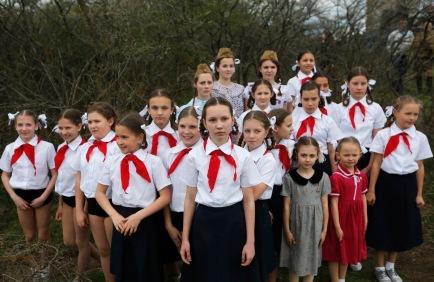 Girls, dressed in the uniform of Soviet pioneers